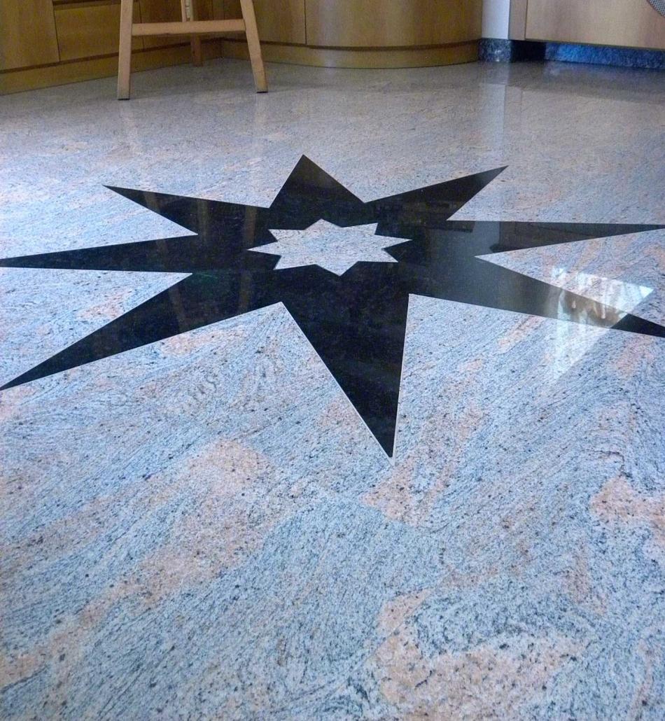 Pavimento in marmo con stella intarsiata